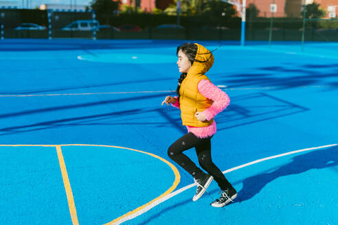 Girl running on blue sports court during sunny day - ERRF04667