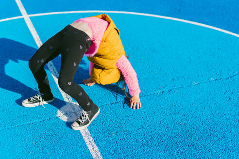 Girl doing acrobatic activity on soccer court during sunny day - ERRF04670