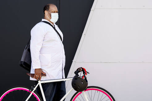 Mature man wearing protective face mask standing with bicycle by wall - GGGF00025