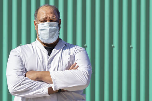 Mature man with arms crossed standing against green metal wall on sunny day - GGGF00031