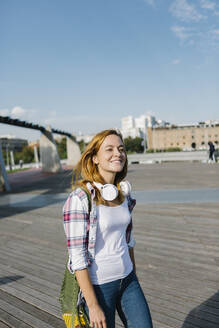 Happy woman looking away with headphone around her neck walking on footpath during sunny day - XLGF00685