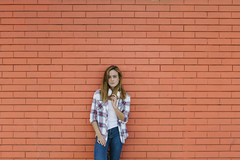 Young woman with headphone around her neck standing against brick wall - XLGF00691