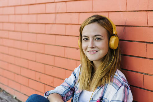 Smiling woman listening music through headphone sitting against brick wall - XLGF00697