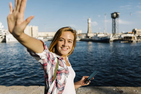 Woman waving while holding smart phone standing at seaside on sunny day - XLGF00706