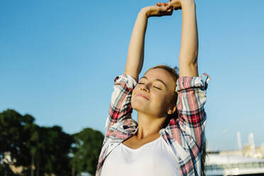 Woman with arms raised stretching hand standing against clear sky on sunny day - XLGF00721