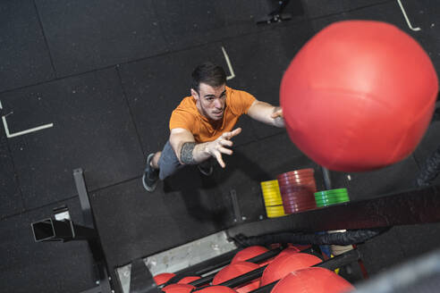 Mid adult man throwing fitness ball while standing in gym - SNF00704