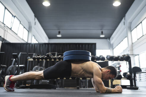 Male athlete doing plank position in health club - SNF00734