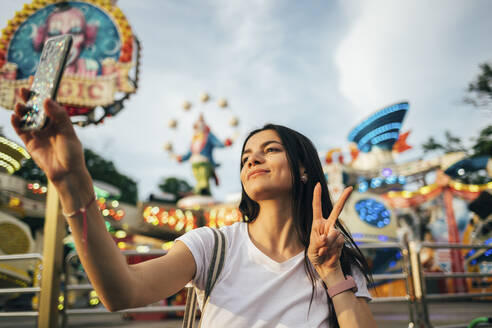Beautiful young woman taking selfie through smart phone while gesturing peace sign at amusement park during summer - OYF00232