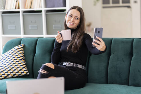 Smiling beautiful female blogger taking selfie with coffee cup while sitting on sofa at home - GIOF09421