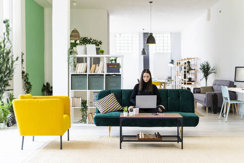 Young female influencer blogging through laptop while sitting on sofa at loft apartment - GIOF09424
