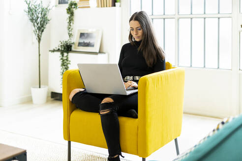 Young woman using laptop for blogging while sitting on chair at home - GIOF09430