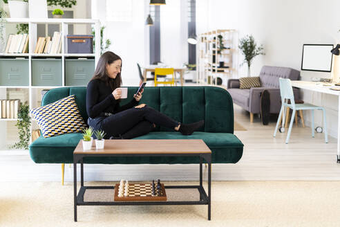 Smiling female blogger using phone while sitting with coffee cup on sofa at home - GIOF09433