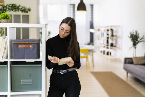 Beautiful young woman reading book while standing by rack at home - GIOF09442