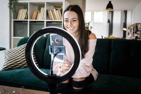 Smiling beautiful female influencer sitting on sofa while vlogging through smart phone at home - GIOF09454