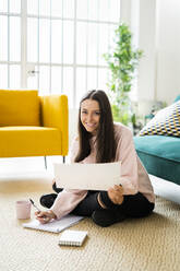 Happy beautiful young woman sitting with note pads and coffee cup on carpet against sofa at home - GIOF09472