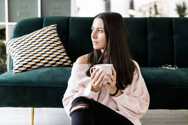 Thoughtful young woman looking away while sitting with coffee cup against sofa at home - GIOF09475