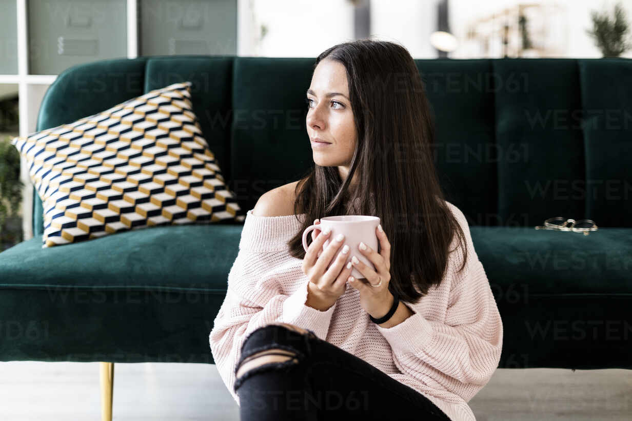 Thoughtful young woman looking away while sitting with coffee cup against sofa at home - GIOF09475 - Giorgio Fochesato/Westend61