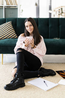 Beautiful young woman sitting with coffee cup and note pads on carpet against sofa at home - GIOF09478