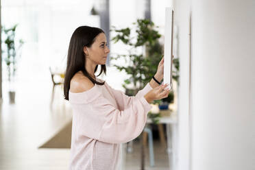 Beautiful young woman adjusting mirror on white wall at home - GIOF09481