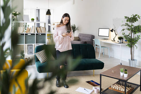 Smiling woman text messaging through smart phone while standing in living room at home - GIOF09484