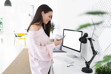 Smiling female influencer using mobile phone while standing at computer desk in loft apartment - GIOF09487