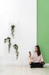 Young woman taking selfie through smart phone while sitting on floor by ladder against wall - GIOF09493