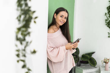 Smiling beautiful young woman holding smart phone while leaning on wall - GIOF09496