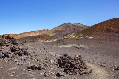 Senior man hiking along trail stretching across brown barren landscape of Tenerife island - WWF05558