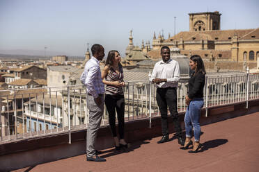 Smiling male and female entrepreneurs discussing on rooftop of office building during break - LJF01790