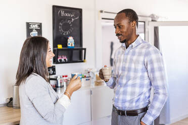 Smiling male and female entrepreneurs talking while having coffee during break in office - LJF01811