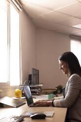 Smiling female entrepreneur using laptop at desk in office - LJF01820