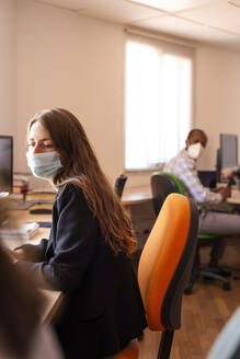 Businesswoman in protective face mask working at desk in office - LJF01829
