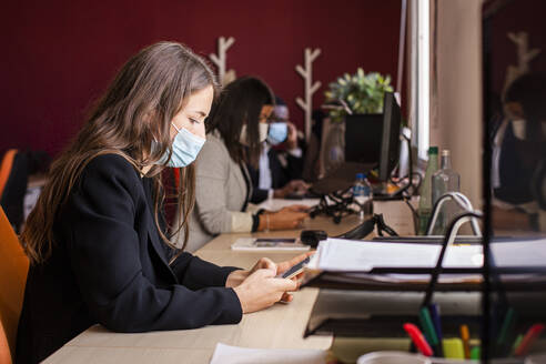 Young businesswoman in protective face mask text messaging through smart phone at desk in office during pandemic - LJF01832