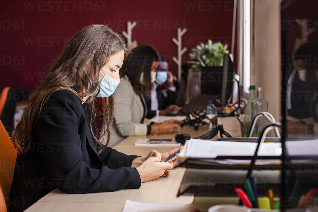 Young businesswoman in protective face mask text messaging through smart phone at desk in office during pandemic - LJF01832 - DREAMSTOCK1982/Westend61