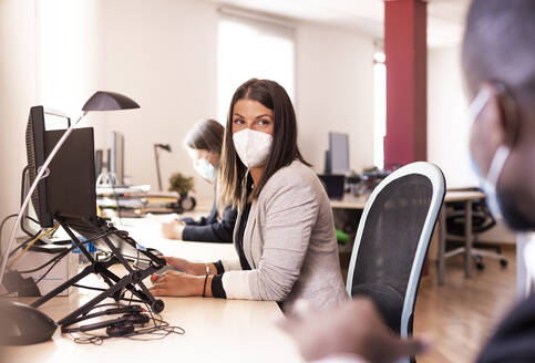 Female business in face mask looking at colleague while sitting at desk in office during COVID-19 - LJF01838
