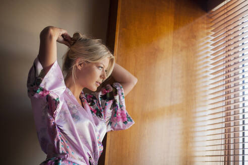 Beautiful woman in bathrobe tying hair while looking through window at home - AJOF00483
