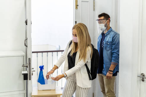 Blond woman wearing face mask washing hands while standing with coworker in background at office - MPPF01178