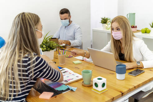 Women wearing face mask talking while sitting with coworkers in background at office - MPPF01184