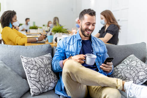 Smiling man holding coffee cup and mobile phone while sitting with coworker in background at office - MPPF01199