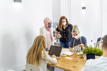Employee wearing face mask while working at office - MPPF01220
