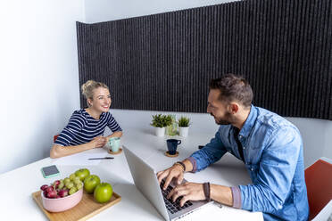 Smiling male and female coworker working on laptop while sitting at office - MPPF01235