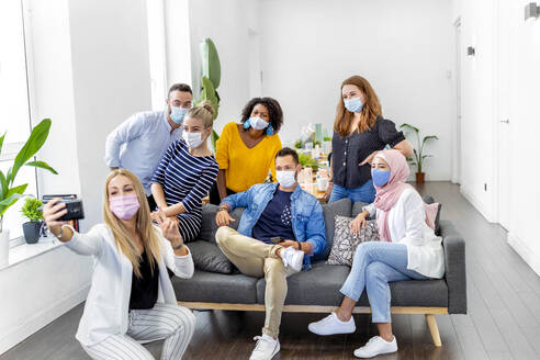 Woman wearing face mask taking selfie with coworker while crouching at office - MPPF01238