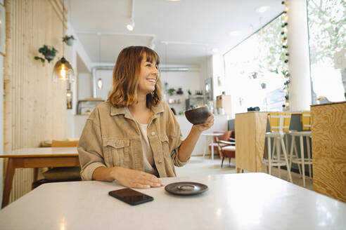 Businesswoman looking away while holding coffee cup sitting in cafe - GUSF04549
