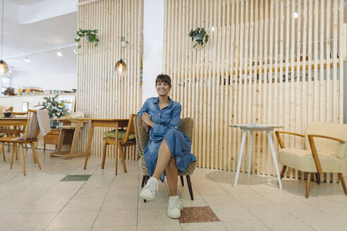 Businesswoman sitting on chair in cafe - GUSF04561