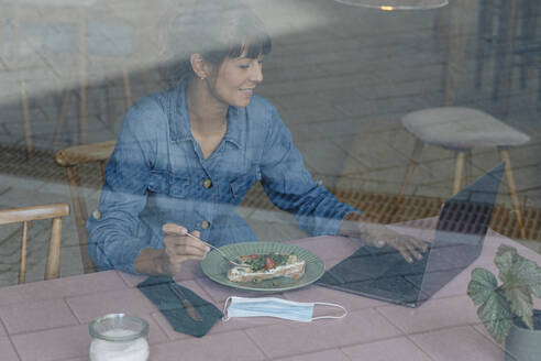 Female entrepreneur eating food while using laptop seen through window sitting in cafe - GUSF04567