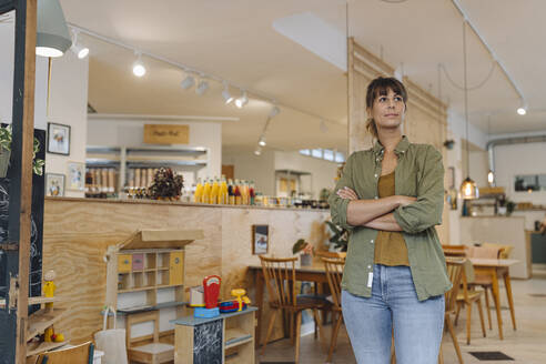 Female owner with arms crossed looking while standing in cafe - GUSF04585