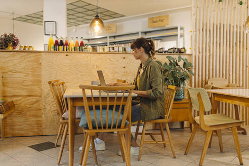 Female owner working on laptop while sitting in cafe - GUSF04591