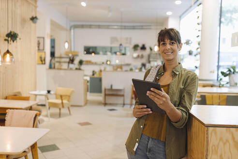 Smiling female owner using digital tablet standing in coffee shop - GUSF04594
