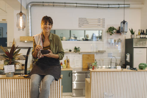 Smiling female owner holding coffee cup sitting on counter in cafe - GUSF04600