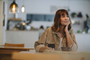 Female owner with hand on chin holding smart phone sitting in cafe - GUSF04609
